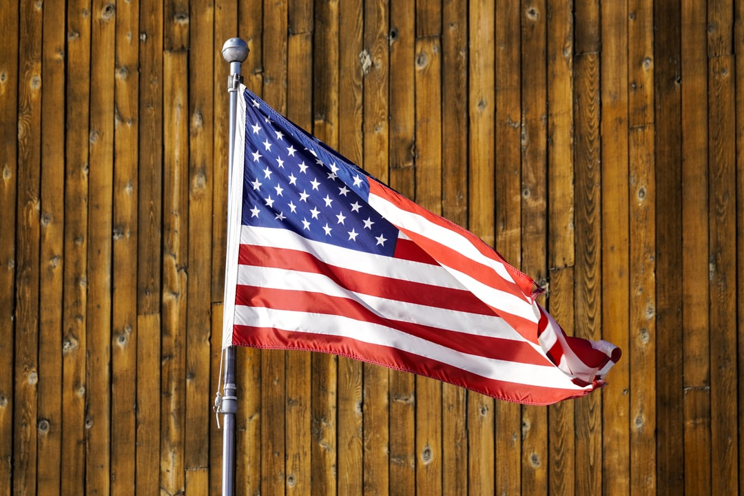 A flag on top of a wooden fence